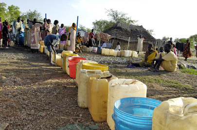 Internally Displaced Persons Wait in Line to Pump Water