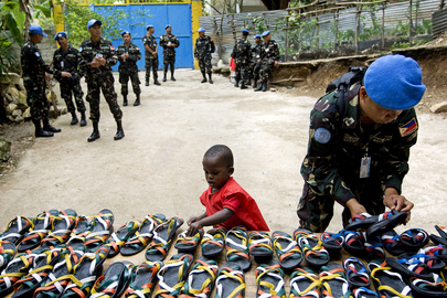 Haitian Child Helps MINUSTAH Peacekeeper Organize Shoes