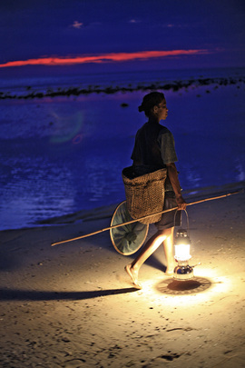 Woman Collecting Fish at Sunset in Dili District