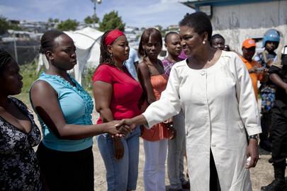 Chefe humanitária da ONU, Valerie Amos (à direita), sendo cumprimentada por moradores do acampamento Accra no Haiti, durante a sua visita em setembro de 2011.