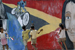 Children Playing in Front of Mural Promoting Tour-de-Timor Cycle Race 9.922653