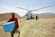 Un homme porte une caisse. Un hélicoptère à l'arrière plan.