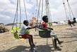 Haitian Children Play on Amusement Park Ride Near Camp 9.641286